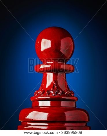 Macro Image Of A Wooden Chess Pawn In Red With Blue And Black Background