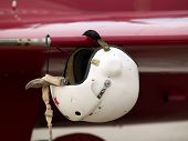 Pilot's air helmet on pitot tube on airplane's wing poster