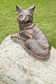 Cute statue of a fox sitting on the rock. poster