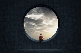 Man With A Backpack Looking Through A Round Concrete Window To Sunset Sky.