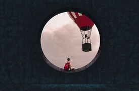 Man With A Backpack Looking Through A Round Concrete Window To A Hot Air Balloon Flying.
