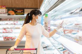 Asian Woman With Hygienic Mask And Rubber Glove With Shopping Cart In Grocery And Looking For Fresh