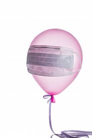 Pink Balloon With Medical Mask On It Hanging On Air On White Wall. Protection Against Virus Or Flu.