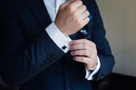 Close Up Of A Man In A Tux Fixing His Cufflink