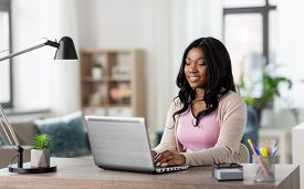 remote job, technology and people concept - happy smiling african american young woman with laptop computer working at home office