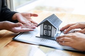 Estate Agent Are Presenting Home Loan And Giving House To Client After Discussing And Signing Agreem