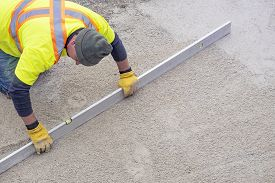 Workman In Yellow Safety Vest Using A 10 Foot Level Tool To Measure The Evenness Of A Patio Foundati