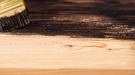 Wooden Boards Are Half Covered With Stain. A Brush With A Wooden Handle And Natural Bristles On A Ba