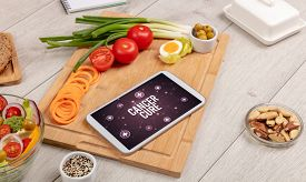CANCER CURE concept in tablet pc with healthy food around, top view