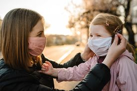 Coronavirus The End Concept. No More Covid-19. Little Girl, Mother Wear Masks Walk On Street. Mom Re