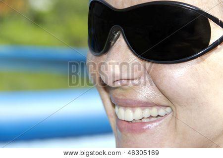 太阳镜微笑的女人的脸上