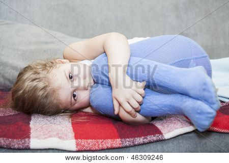 Little Caucasian Defenseless Child Huddled On The Couch