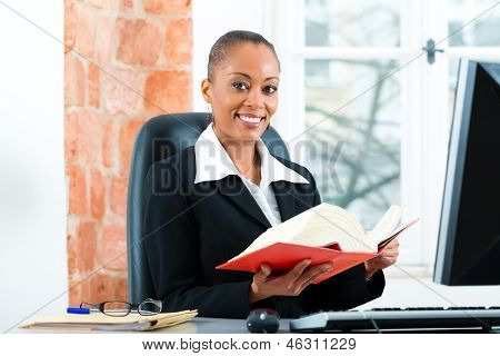 Young female lawyer working in her office with a typical law book and writing on the Computer poster