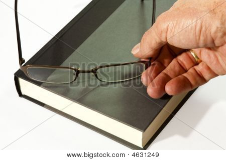 Book And Eyeglasses In Hand