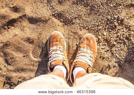 Pair of Boots Shoes man's Foot on a sand sea-side beach view from above Summer Leisure time background poster