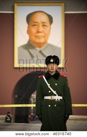 BEIJING, CHINA-DECEMBER 27: A guard is standing in front of the Tiananmen gate. The portrait of Mao Tse Tung hangs on the wall in the background. on December 27, 2011 in Beijing, China.