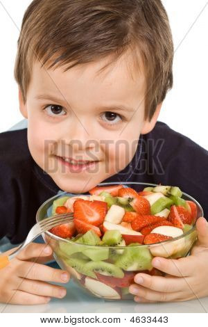 Little Smiling Boy With A Bowl Of Sliced Fruits