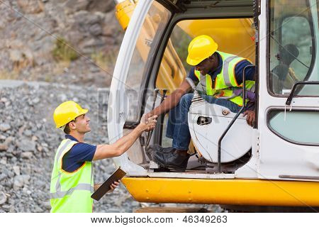 happy construction manager handshaking with bulldozer operator at construction site poster