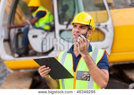 construction foreman talking on walkie-talkie holding clipboard