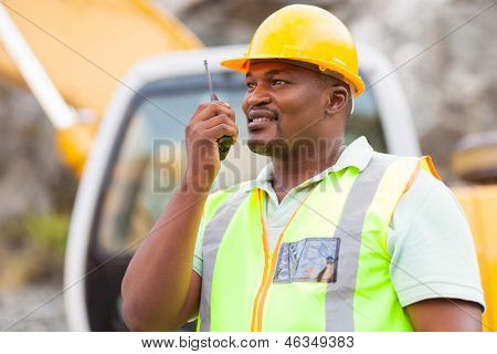 afro american industrial worker talking on walkie-talkie at mining site