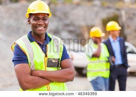 glücklich afrikanischen Industriearbeiter mit Armen gefaltet