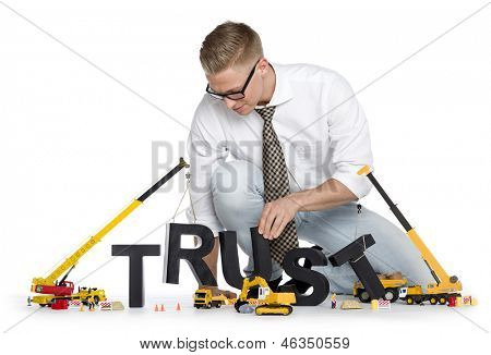 Build up trust concept: Focused businessman building the word trust along with construction machines, isolated on white background.