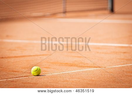 single tennis ball on tennis court