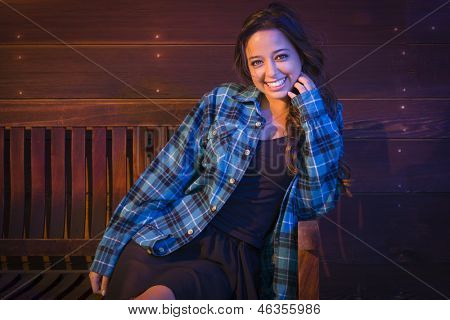 Portrait of a Pretty Mixed Race Young Adult Woman Sitting on Wooden Bench Against a Lustrous Wood Wall Background.