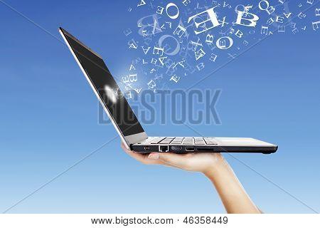 Letras del alfabeto volando desde el exterior de la pantalla del ordenador portátil