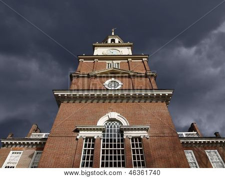 Brick clock tower with dark storm sky at historic Independence Hall National Park in Philadelphia.