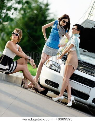 Group of three girls near the broken car with the opened hod waiting for help poster