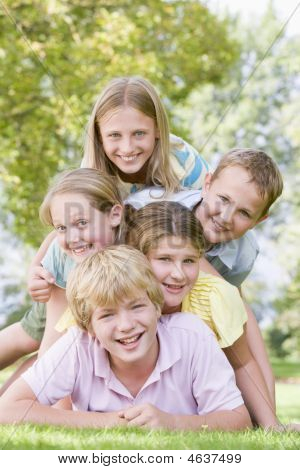 Five young friends piled on each other outdoors smiling poster