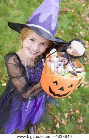 Young Girl Outdoors In Witch Costume On Halloween Holding Candy