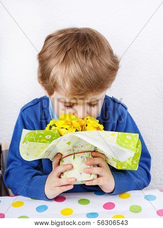 Cute Lovely Toddler Boy Of 3 Years Sniffing Yellow Flowers For Mothersday
