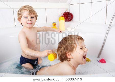 Two Little Twins Boys Having Fun With Water By Taking Bath In Bathtub.