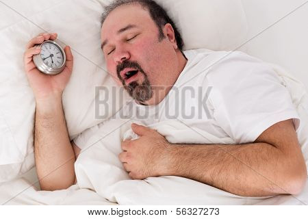 Lethargic tired man lying in bed yawning as he struggles to wake up unmotivated to start the new day and content to rather continue lying in bed as he holds his alarm clock in his hand poster