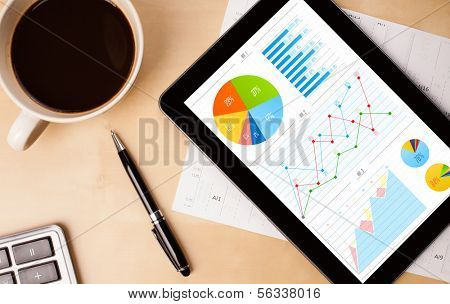 Workplace with tablet pc showing charts and a cup of coffee on a wooden work table close-up