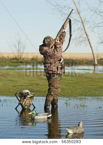 A young hunter taking aim at a duck poster