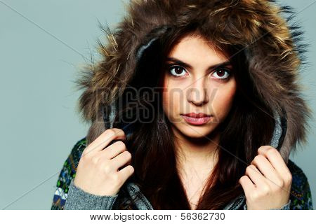 Closeup portrait of a young pensive woman in warm winter outfit on gray background