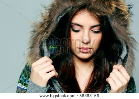 Closeup portrait of a young woman in warm winter outfit with closed eyes