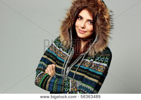 Young happy smiling woman in warm winter outfit on gray background