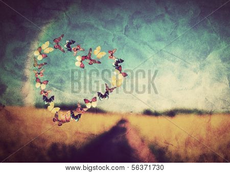 Heart shape made of colorful butterflies on vintage field background. Love, hope concept.