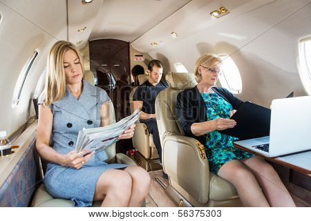 Business people traveling in corporate jet