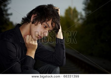 Poor Young Man Sitting On The Railway