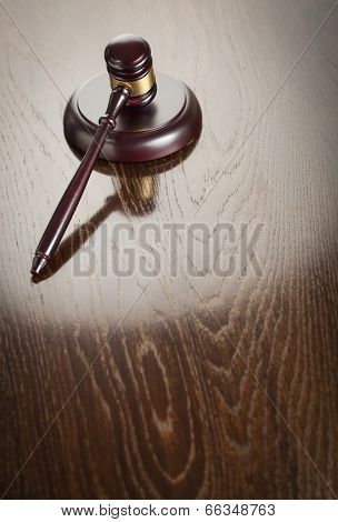 Dark Wooden Gavel Abstract on Reflective Table with Room for Text.