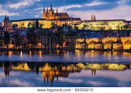 Prague Castle and Charles Bridge at sunset with reflection on Vltava river