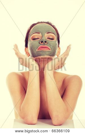 Beautifu toplessl woman with facial mask having her eyes closed.