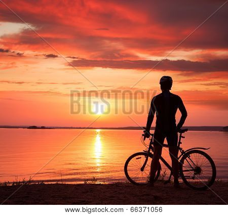 Man Standing with a Bike at Sunset
