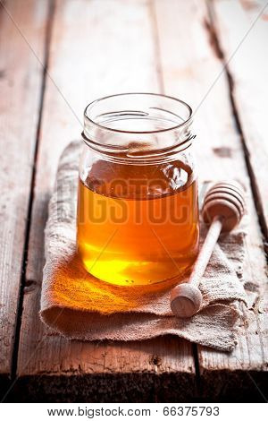 full honey pot and honey stick on rustic wooden board