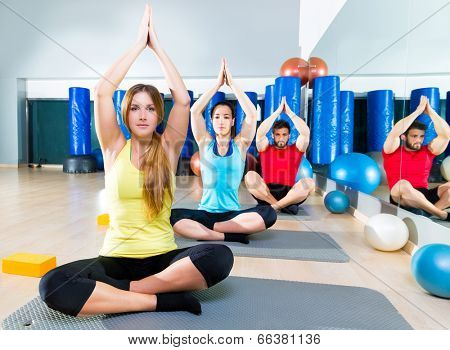 Yoga training exercise in fitness gym people group relaxed hands up
